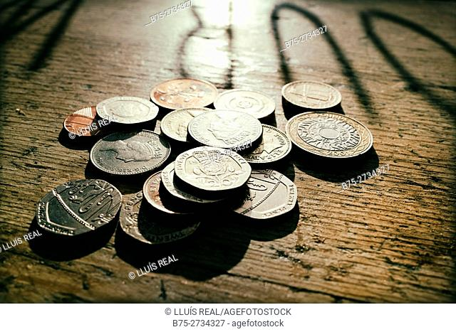 English coins on a rustic table. London, England