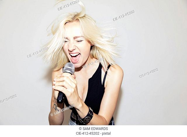 Exuberant young woman singing into microphone