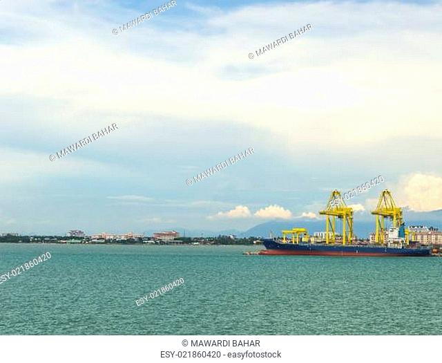 Cargo ship loading container againts cloudy scene