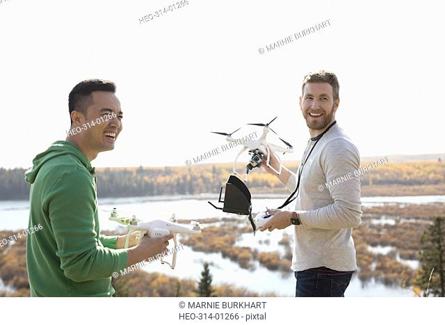 Smiling male friends with drone equipment overlooking lake