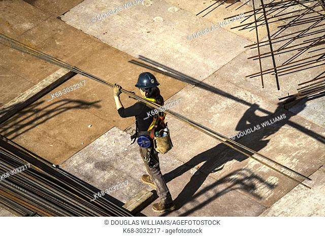Construction worker carries steel bars at Vancouver House, a tower under construction in Vancouver, BC, Canada