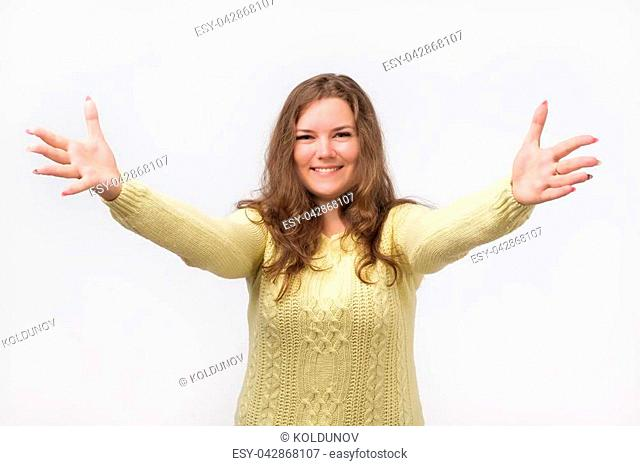 portrait of attractive smiling caucasian woman raised up arms hands at you. She is dressed in yellow sweater. Happy to welcome a friend or guest