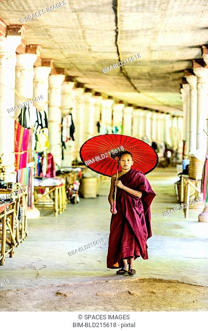 Asian monk-in-training with parasol walking in hallway