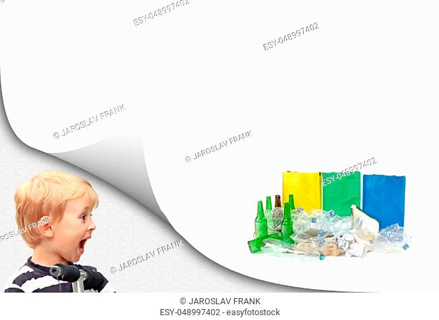 Surprised blond boy is looking at a pile of sorted waste with ready colored bags on the white background ready for your text