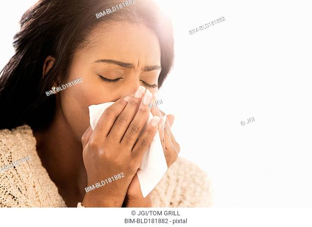 Mixed race woman blowing her nose