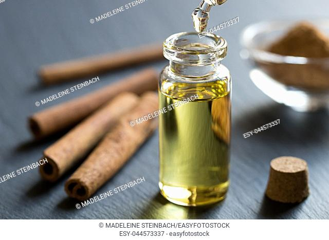 A drop of cinnamon essential oil is being dropped into a bottle, with cinnamon sticks and powder in the background