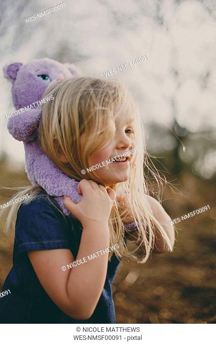 Smiling girl carrying a teddy outdoors