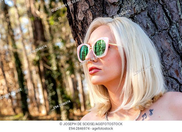 Portrait of a 30 year old blond woman wearing large sunglasses, looking away from the camera, outdoors