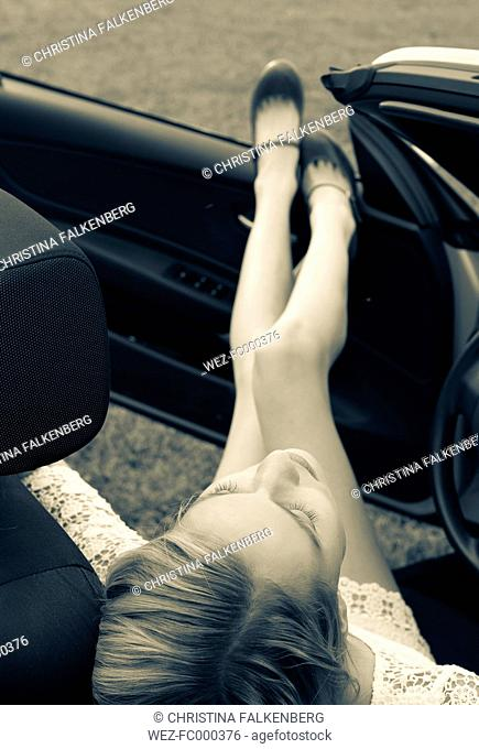 Young woman sitting in cabriolet with feet up, elevated view