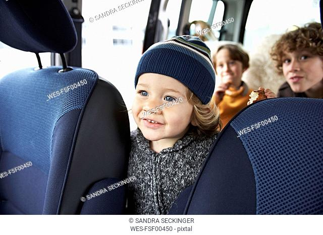 Little boy sitting in car with brothers