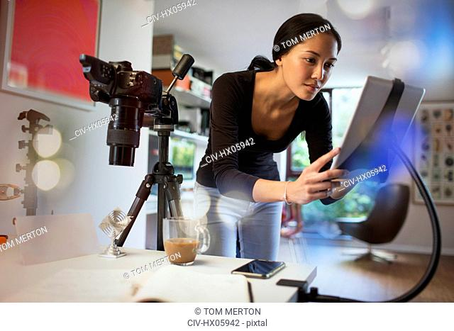 Female photographer working in studio, using digital tablet