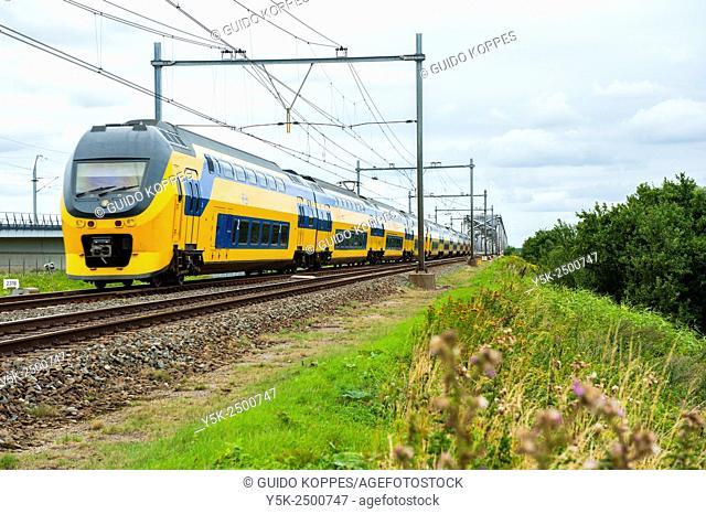 Moerdijk, Netherlands. Double deck intercity train passing the 1950's build railroad bridge over ethe river Hollandsch Diep