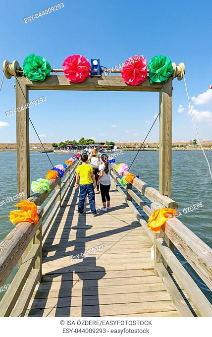 Unidentified People walk on wooden bridge decorated for bride and groom in Kucukcekmece Lake. TURKEY, ISTANBUL,30 JULY 2017