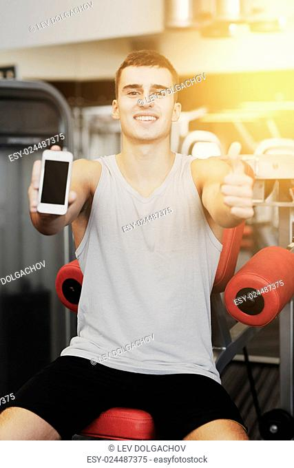 sport, bodybuilding, lifestyle, technology and people concept - smiling young man showing smartphone and thumbs up gesture in gym