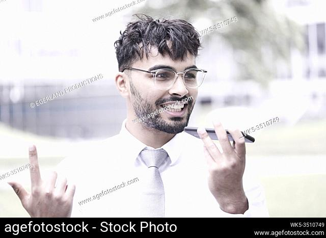 optimistic businessman on the street, talking on phone, pointing up