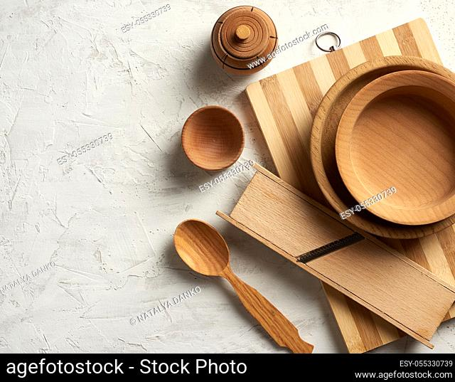empty wooden round plates and new cutting board on gray background, top view, copy space