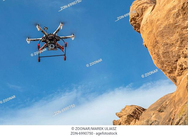 drone flying along sandstone cliff