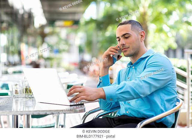Caucasian businessman talking on cell phone in cafe