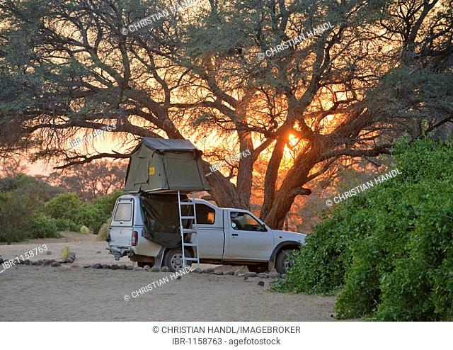 Off-road vehicle with a rooftent, sunset in the camp of the White Lady Lodge at Mt Brandberg, Namibia, Africa