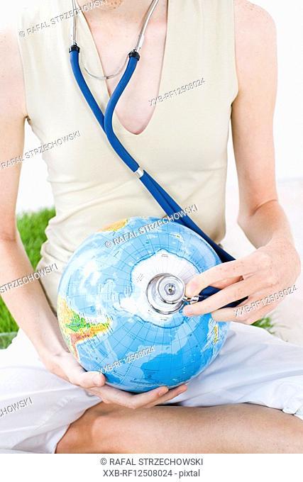 young woman examinating globe