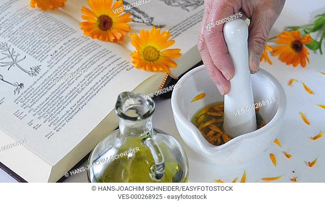 mixing a calendula flower in a mortar with olive oil for a beauty remedy