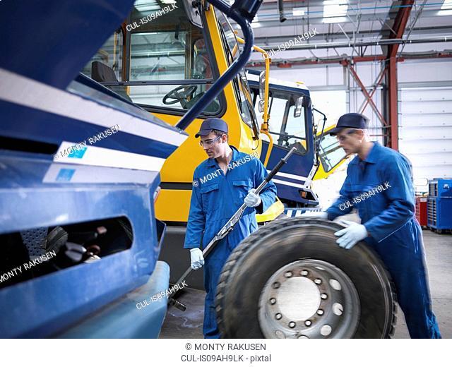 Engineers prepare to fix wheel in truck repair factory
