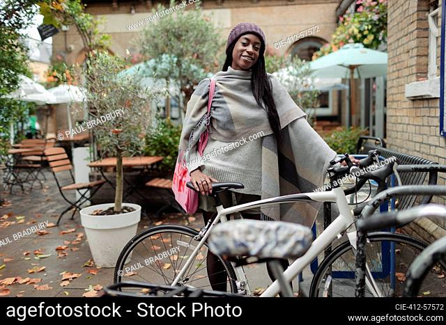 Portrait confident young woman with bicycle on cafe patio