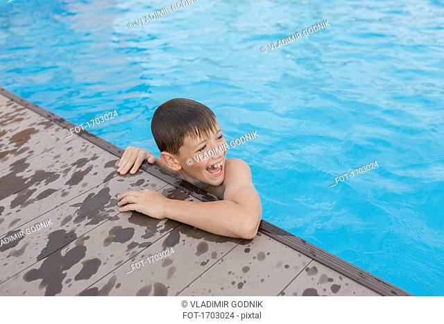 High angle view of cheerful shirtless boy swimming in pool
