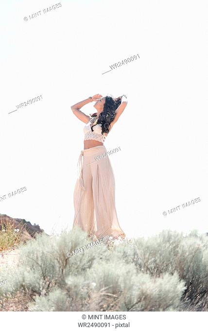 Young woman with long brown hair, wearing a long white dress, standing in the prairie