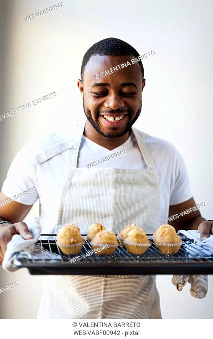 Happy young man holding tray with muffins