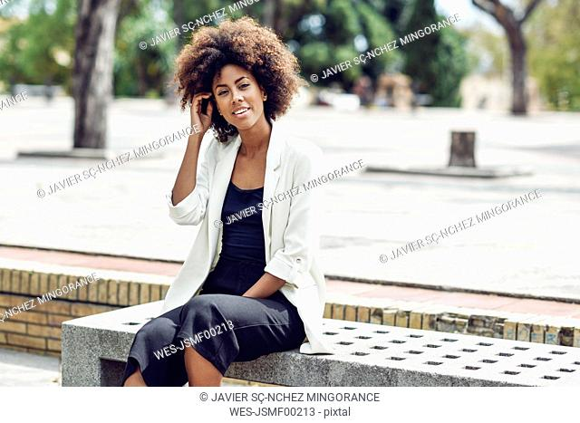 Portrait of smiling young woman with curly hair sitting on bench