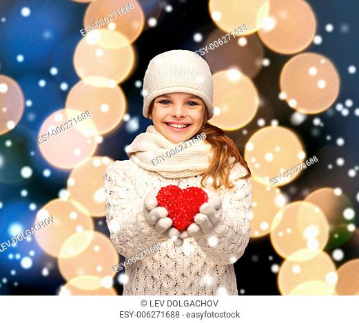 charity, happiness and love concept - smiling teenage girl in winter clothes with small red heart