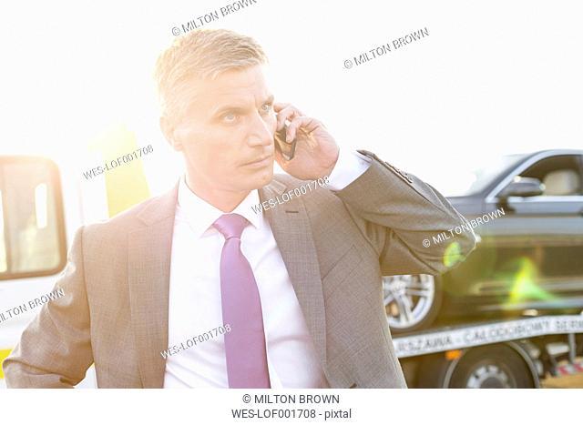 Businessman on cell phone having a car breakdown