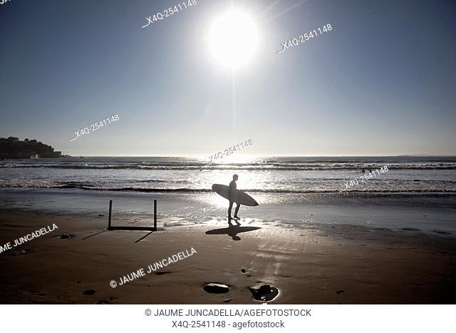 Surfer walks along the beach after a fun time in the water. Image is backlit and features the subject in silhouette