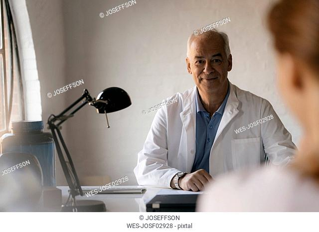 Senior doctor looking at female patient in medical practice