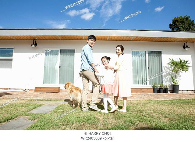 Family with a pet dog at the yard of their house in Jeju representing rural life