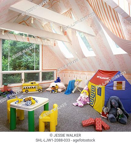 CHILDREN'S PLAYROOMS: Child's play area in attic, cathedral ceiling, white and pale pink, drapes hang from skylights. Plastic furniture, cloth play house