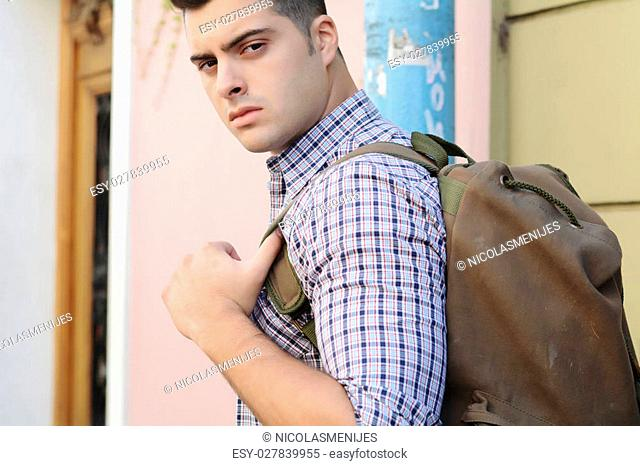 Young male student with his bag outdoors