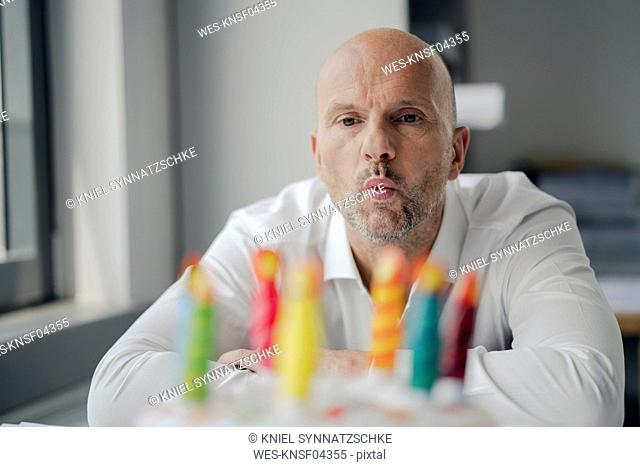Businessman celebrating his birthday in the office, blowing out candles