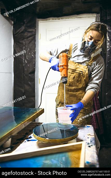 Female resin artist mixing with respirator mask