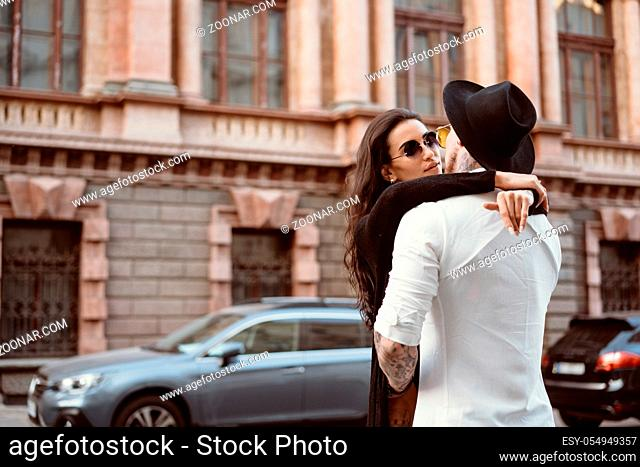 A young, sexy couple of lovers pose for a camera on the streets of the city