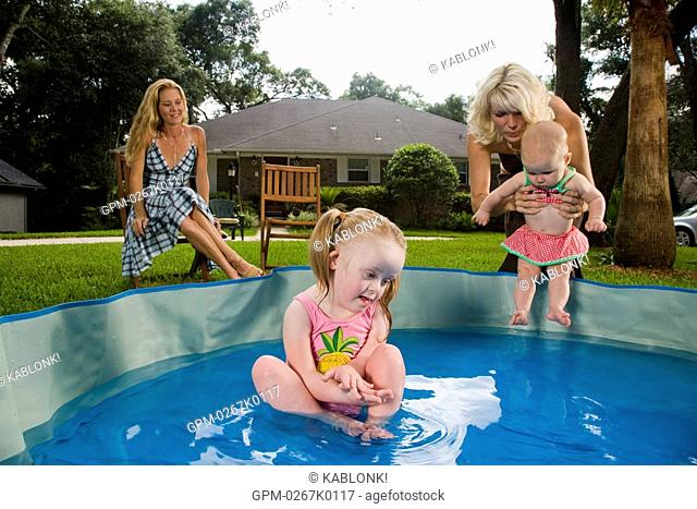 Girl with downs syndrome playing in kiddie pool with family watching