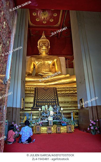 Woman and child praying in front of a big golden Buddha in Wihan Mongkhon temple. Thailand, Ayutthaya, Wihan Mongkhon