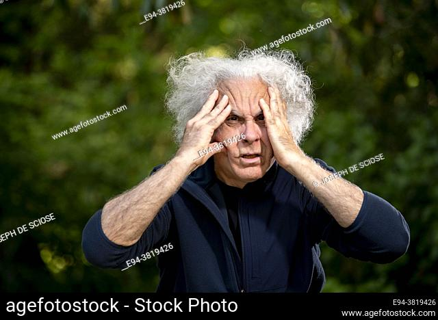 A grey haired 68 year old man making a face and pulling his hair out. ,