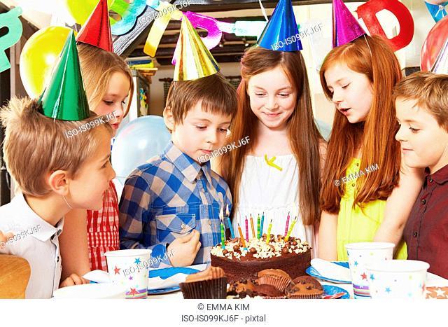 Children around cake at birthday party
