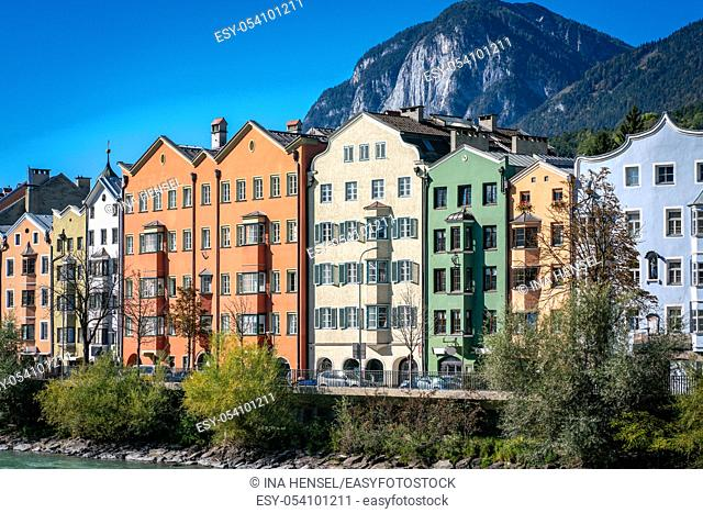 Panoramic view of colourful buildings in the austrian town Innsbruck with the river Inn in the foreground and mountainsof the alps in the background on a sunny...