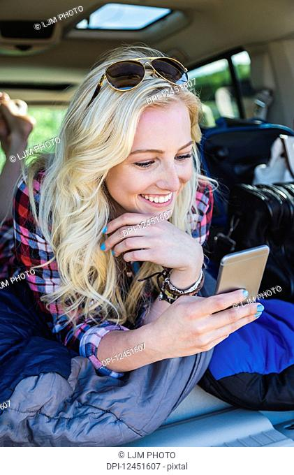 A young woman on a road trip lays in the back of a vehicle with a sleeping bag using her smart phone; Edmonton, Alberta, Canada