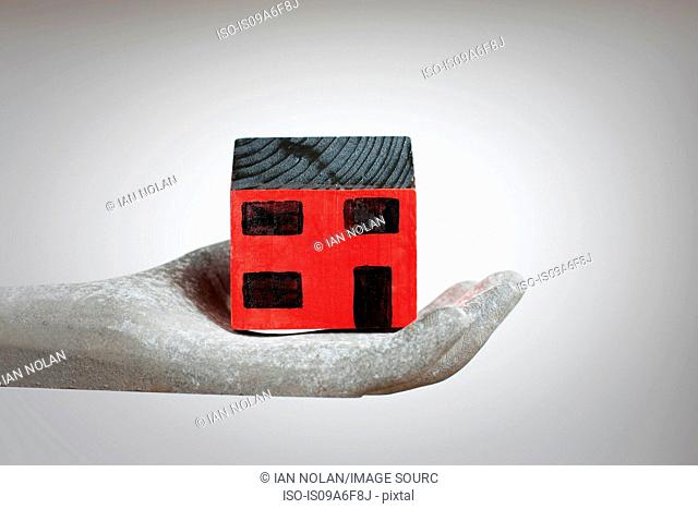 Hand holding model of house