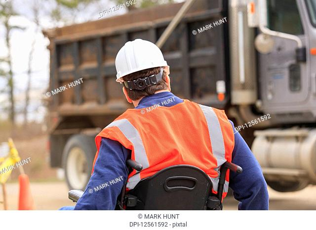 Construction engineer with spinal cord injury watching equipment operator