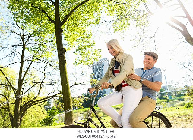 Mature couple riding bike in park, man sitting on rack